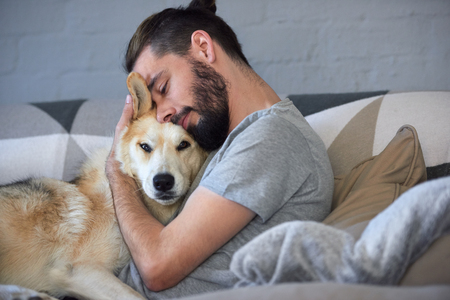hipster man snuggling and hugging his dog, close friendship loving bond between owner and pet husky Stockfoto