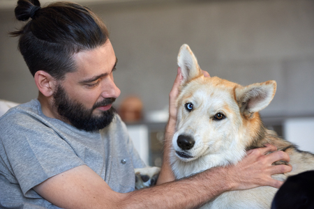 topknot: hipster man petting and rubbing his dog, loving affection best friend bond between owner and pet Stock Photo