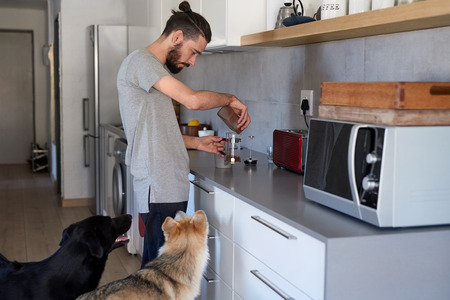 topknot: young hipster man making coffee at home kitchen with his pet dogs sitting by him