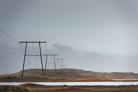 voltage: High voltage power lines electric pylons over land, in misty cloudy stormy landscape with mountains in the background Stock Photo