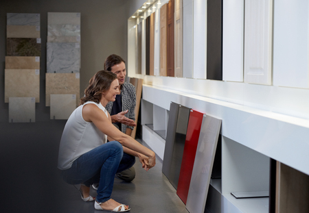 Couple examining different materials and samples in contemporary kitchen shop showroom while designing their dream kitchen Banco de Imagens