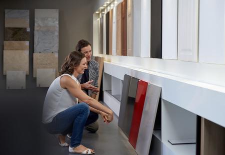 Pár zkoumání různých materiálů a vzorků v současném showroomu v kuchyni při projektování jejich vysněné kuchyně