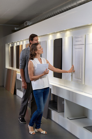 Couple walking through modern kitchen showroom looking at different types styles of cabinets