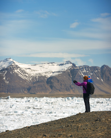 Woman traveller taking a photo of Jokulsarlon glacier Lagoon with iceland flag flapping in the wind, snowcapped mountains in the background photo