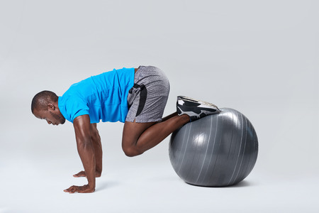 body toning: Fit healthy man uses pilates gym ball as part of toning and muscle core building training exercises