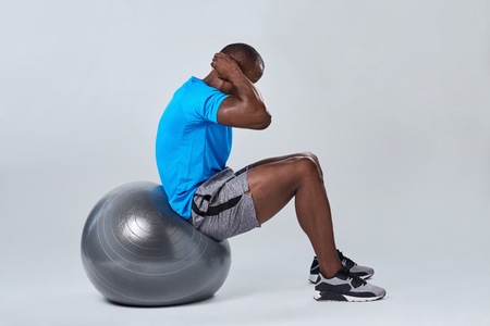 muscle toning: Fit healthy man uses pilates gym fitness ball as part of toning and core muscle building training exercises Stock Photo