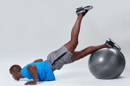 muscle toning: Fit healthy man uses pilates gym ball as part of toning and muscle building training exercises