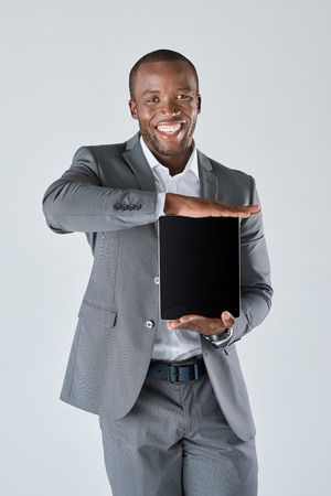 african business man: Confident african black business man with touchscreen tablet device in business suit isolated in studio Stock Photo