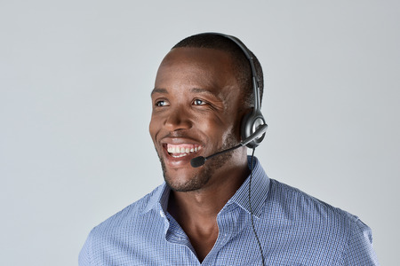 microphone headset: African man customer service personnel operator smiling with microphone headset
