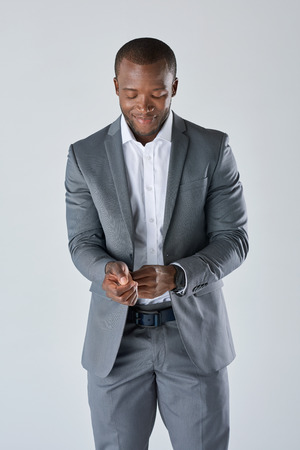 dapper: Candid portrait of african business man in grey suit adjusting his suit jacket Stock Photo