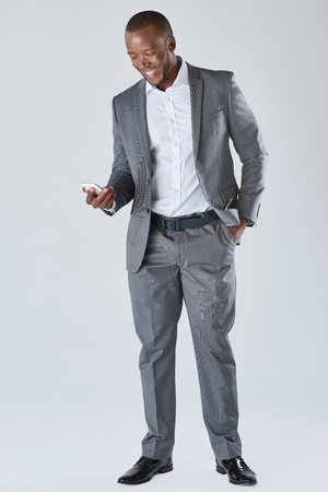 formal attire: Black professional businessman in business formal attire on his mobile cell smartphone