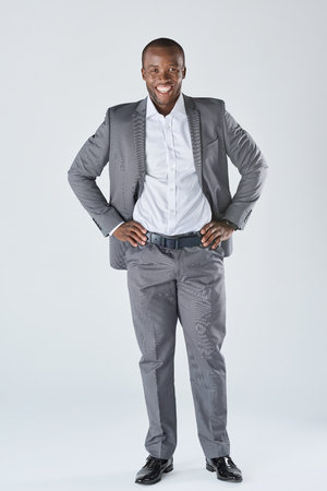 approachable: Full length portrait of approachable smiling black  professional in business suit isolated in studio
