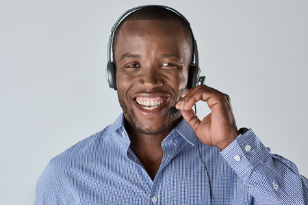 telemarketer: African man operator salesman telemarketer smiling with microphone headset