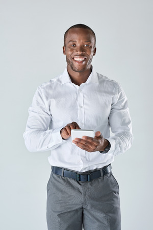 young guy: Black professional business man talking on his mobile cell phone having a conversation in studio