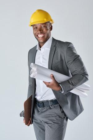 Glimlachend portret van Afrikaanse zwarte van de de adviseursholding van de bouwtechniek de tekeningsplannen en het dragen van een bouwbouwvakker