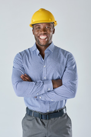 Portrait of black african architect engineer surveyor with construction hardhat isolated in studio