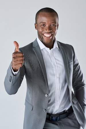 happy african: Smiling happy african black executive professional giving a thumbs up in studio