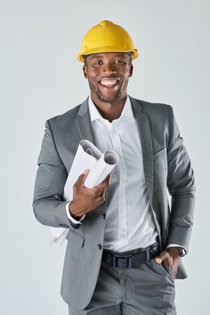 engineer: Confident smiling portrait of african engineer construction consultant holding plans isolated in studio Stock Photo