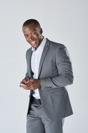 black professional: Black professional businessman in suit on his smartphone in studio