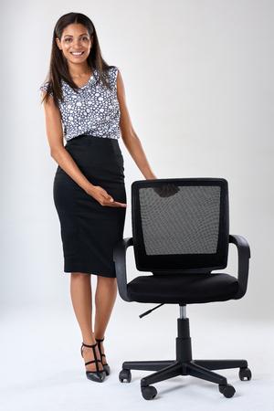 hispanic woman: Pretty friendly hispanic indian asian woman showing a vacant office chair, recruitment hiring employment concept