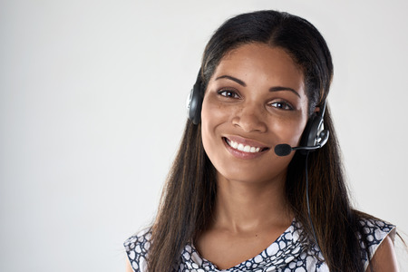 Pretty mixed race woman smiling with headset, isolated in studio Stock Photo