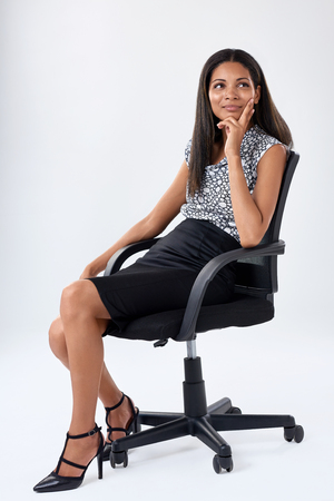 women sitting: young business executive sits on office chair and ponders her career options