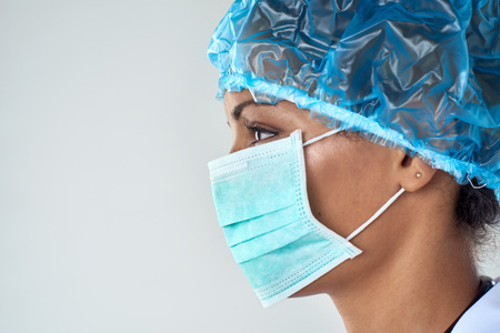 medical procedure: Close up side profile of female surgeon in face mask getting ready for medical procedure surgery