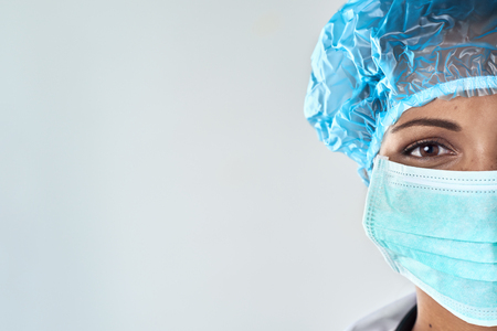 surgeons: Close up of confident female surgeon in mask getting ready for medical procedure surgery Stock Photo