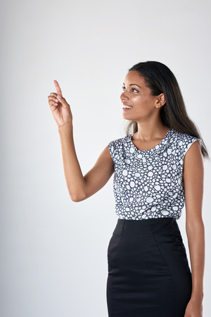 office wear: Beautiful indian business woman in corporate office wear pointing in studio Stock Photo
