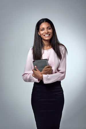 Beautiful indian hispanic latino mixed race corporate business woman holding an  organiser Stock Photo