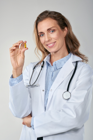 medical cure: Female medical researcher professional smiling and holding up breakthrough drug cure pill, medical and healthcare concept