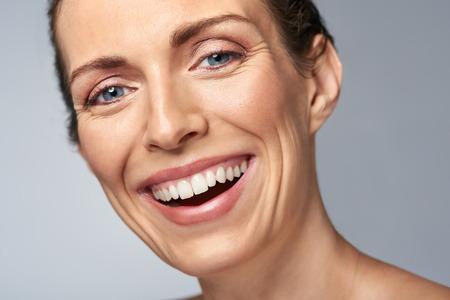 vejez feliz: riendo mujer de mediana edad feliz en estudio, aislado en gris Foto de archivo