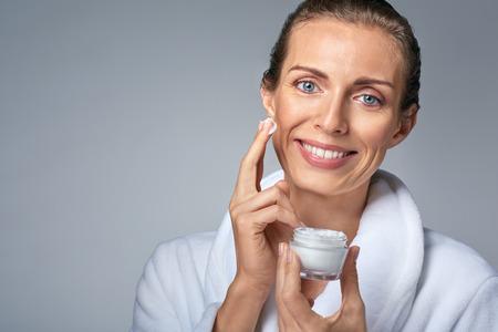 portrait de femme élégante moyenne d'âge en peignoir application de la crème pour le visage, pot à la main