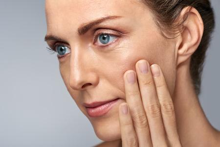 Aantrekkelijke vrouw van middelbare leeftijd te raken haar wang huid, rijp schoonheid concept Stockfoto