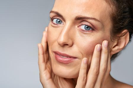Atrakcyjna kobieta dotyka jej twarzy, piękna dojrzała koncepcja