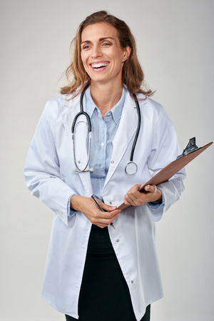 labcoat: Laughing portrait of female doctor isolated on grey background, labcoat and stethoscope and clipboard Stock Photo