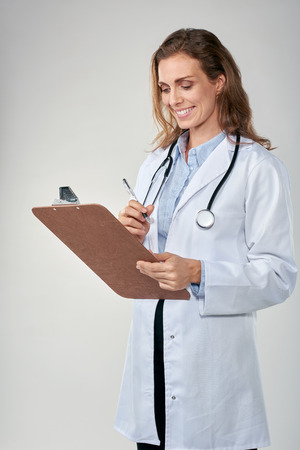 labcoat: Doctor recording patient information on clipboard, isolated on grey background, labcoat and stethoscope and clipboard