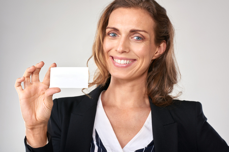 approachable: smiling businesswoman holding a blank card, copyspace for business details