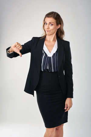 mature women: Businesswoman giving a thumbs down, showing her disapproval  isolated in studio Stock Photo