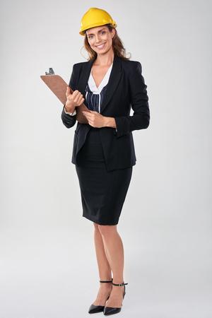 executive helmet: Woman wearing hardhat safety helmet holding clipboard, architect surveyor engineer professional Stock Photo