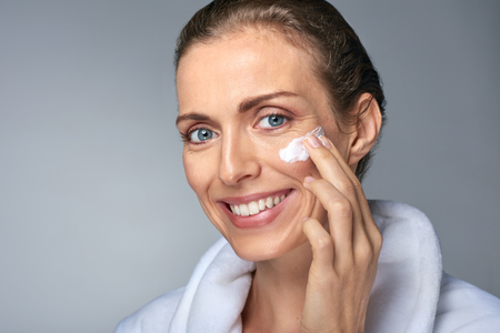 skin care products: portrait of beautiful radiant mature woman applying some cream to her face, skin care cosmetics wellness concept