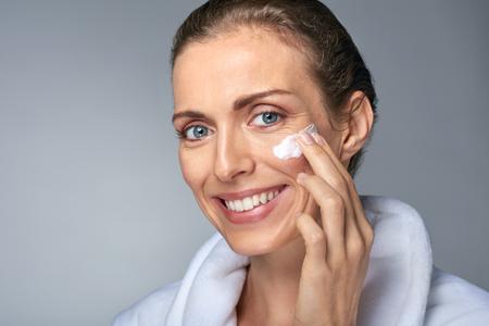 portret van mooie stralende volwassen vrouw het toepassen van enkele crème op haar gezicht, huidverzorging cosmetica wellness-concept