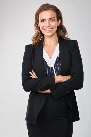 approachable: Portrait of caucasian business woman standing with arms crossed in studio, isolated on grey