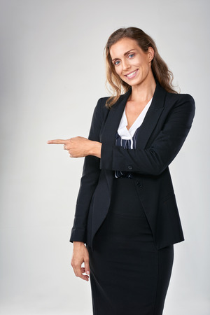 product placement: Woman in business suit pointing to the side isolated in studio, for product placement