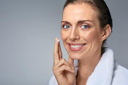 피부 관리를 위해 그녀의 얼굴에 크림을 적용하는 아름다운 여자의 초상화