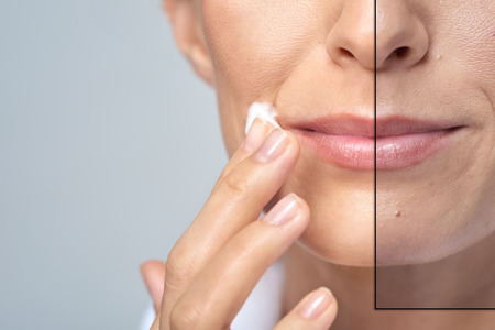 Anonymní žena použití krém na obličej, koncepce studio krásy péče o pleť Reklamní fotografie