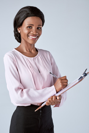 approachable: Beautiful black african corporate business woman writing into an organiser, keeping notes
