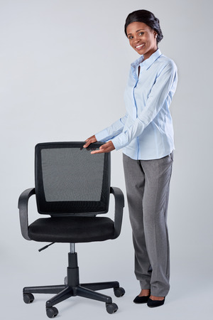 vacant: Pretty friendly african black woman showing a vacant office chair, recruitment hiring employment concept