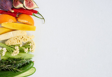 selection: Colourful gradient of healthy fresh fruit and vegetables, fig chilli orange mango pineapple celery rosemary cucumber cauliflower, artistic spectrum