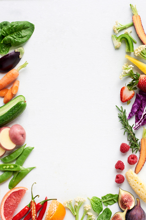 Food background border flatlay of rainbow coloured fresh fruits and vegetables, carrot chilli cucumber purple cabbage spinach rosemary herb, plenty of copy-space